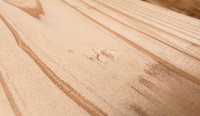 鉛筆の背で無垢材(音響熟成®︎木材)を叩き、意図的に凹み傷を作った